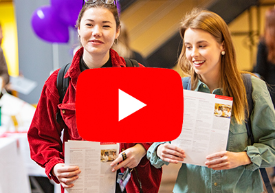 Image of two female students at Preview Day with a play button superimposed. The image acts as a link to a slide show of Grad Studies Preview Day