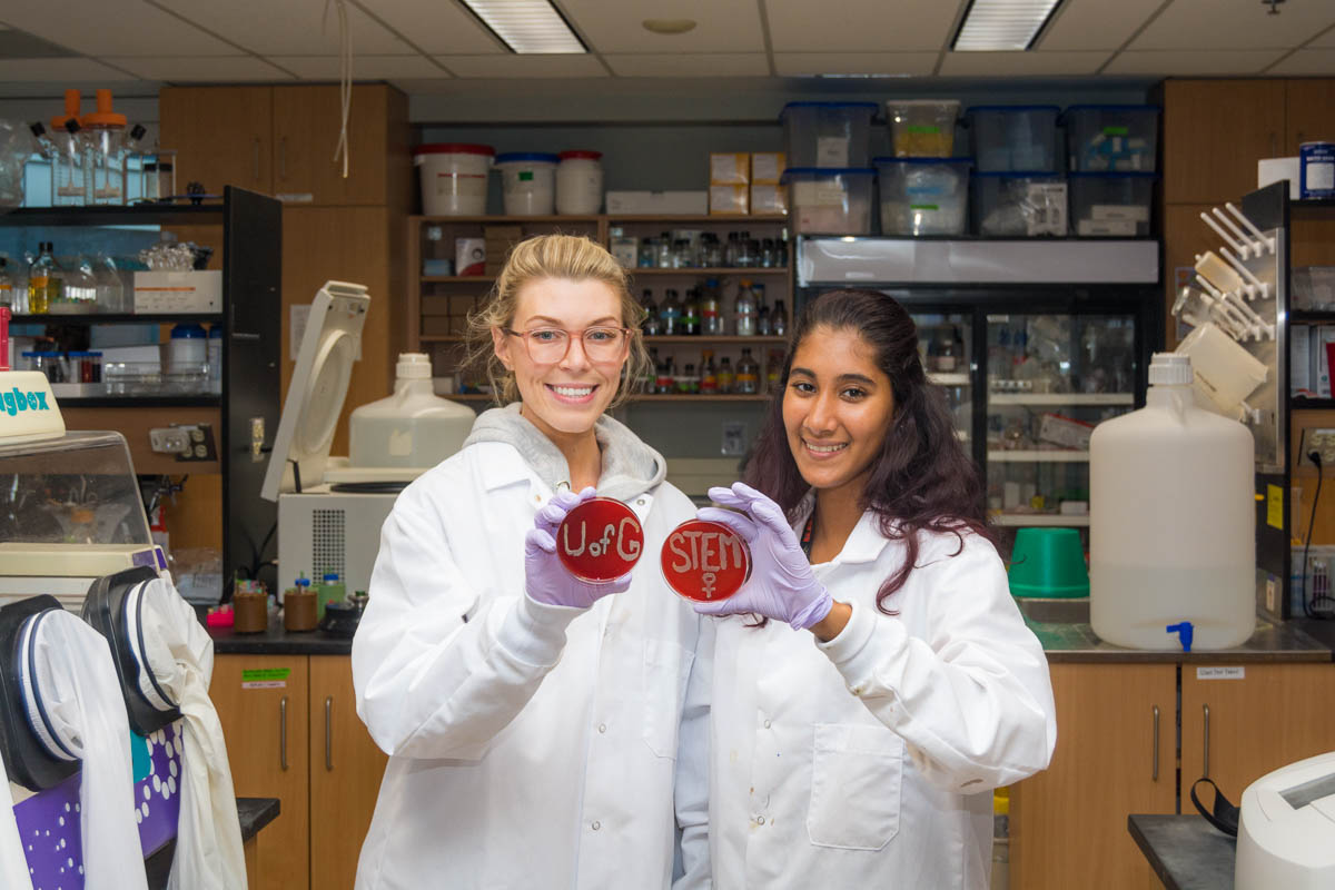 Two female students in a lab holding petrie dishes that say STEM and the sign for female in bacteria