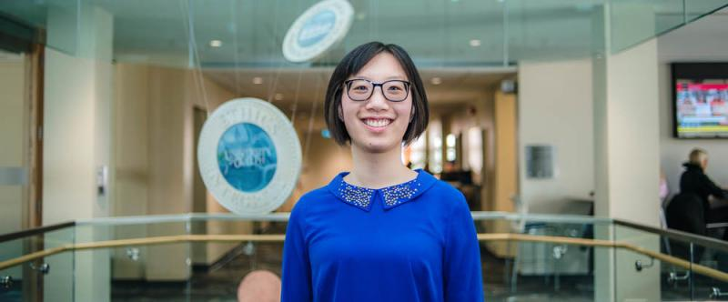 Portrait of graduate student Lydia Wang (MSc, Food Science) in the atrium of Mac Donald Stewart Hall at the University of Guelph