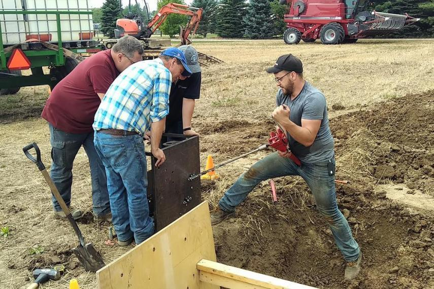Photo of U of G MASc 2016 (Mechanical Engineering) grad, Alex Barrie digging soil with 3 other men