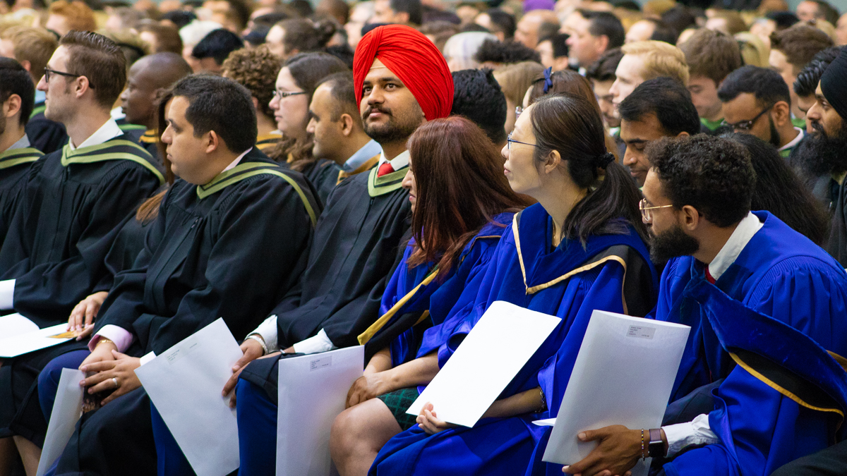 U of G graduates sitting in their gowns during their convocation ceremony