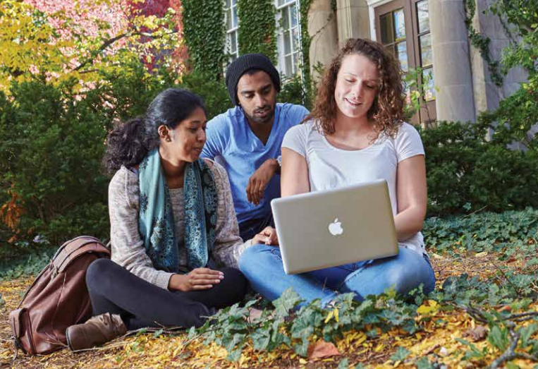 3 students sit outside on campus with a laptop