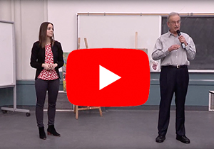 Youtube play icon on a candid from the workshop with Dr. John Bandler and Ana Kovacevic