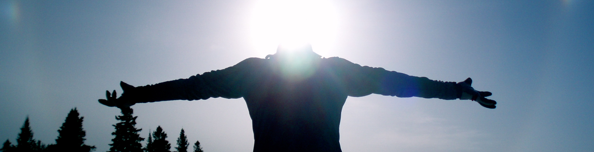 Silhouette of a person with their arms outstretched against the sun & sky
