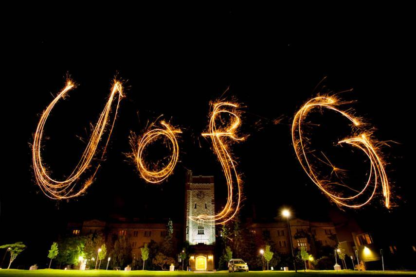 Johnston Hall at night with UofG written in sparklers
